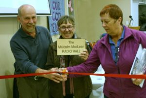 Lee Maclean with Malcolm Maclean's sister Marian Gillanders and spouse cut the red ribbon to rename the Canoe FM Radio Hall to the Macolm Maclean Radio Hall