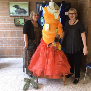 Canoe FM's Janice Andrews and Roxanne Casey viewing the dress that Canoe FM's volunteer Arlene Stiles made and it is on display at the Haliburton Highlands Secondary School h
